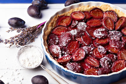 Homemade pie with plums, lavender and sieve with sugar powder on the table with white and blue wooden background. Baked and raw plums. Close view